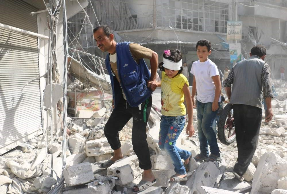 Syrians walk over rubble following airstrikes on the opposition-held Fardous neighbourhood of the northern embattled Syrian city of Aleppo on October 12, 2016.