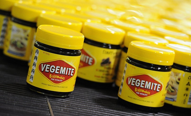 A file photo dated 24 October 2013 shows Vegemite jars rolling along production line at the Vegemite factory in Melbourne, Victoria, Australia (AP Photo)