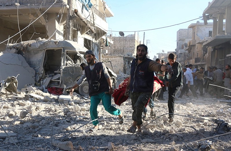 Syrian volunteers carry an injured person on a stretcher following Syrian regime forces airstrikes on the neighbourhood of Heluk in Aleppo, on September 30, 2016. (AFP Photo)