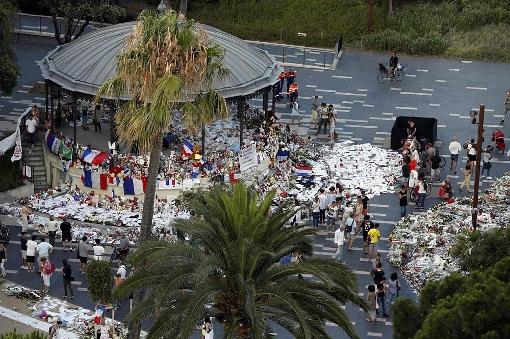 People walk next to floral tributes, notes and candles placed in the road for victims of the deadly Bastille Day attack, on July 20, 2016 in Nice, southern France.  (AFP Photo)