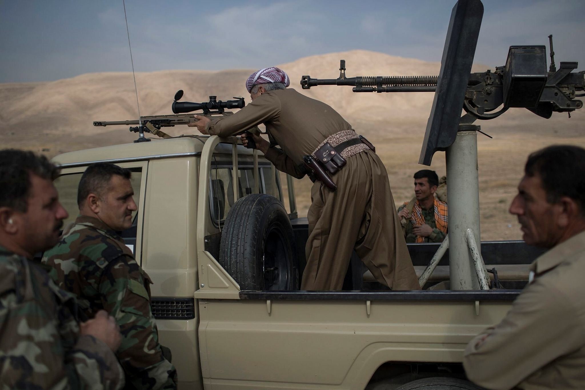 Kurdish Peshmerga fighter looks at Daesh militant positions during heavy fighting in Bashiqa, east of Mosul, Iraq. (AP Photo)