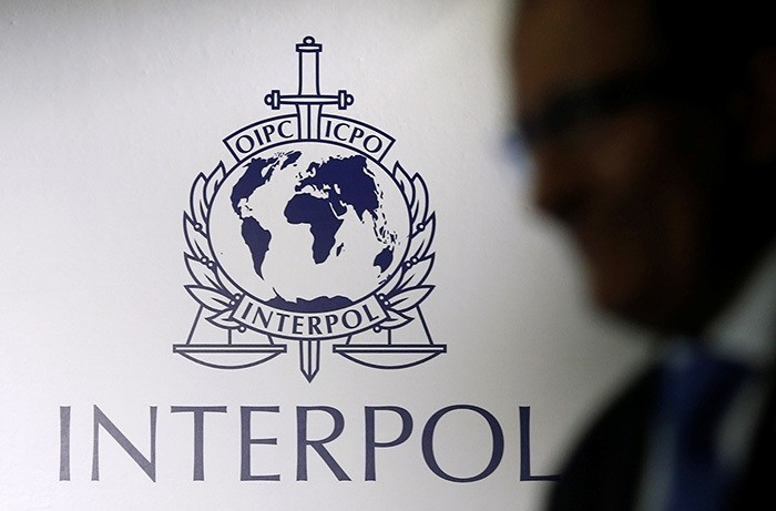 A man passes an Interpol logo during the handing over ceremony of the new premises for Interpol's Global Complex for Innovation, a research and development facility, in Singapore September 30, 2014. (Reuters Photo)