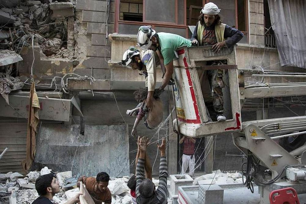 Syrian rescuers hand the body of a girl down to civilians on the ground after she was pulled from the rubble of a bundling following Assad forces airstrikes in the opposition-held neighborhood of Al-Shaar in Aleppo on Sept. 27.