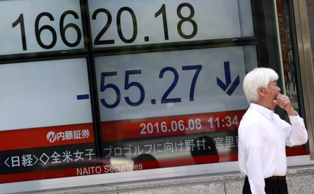 A man stands near an electronic stock board showing Japanu2019s Nikkei 225 index at a securities firm in Tokyo.