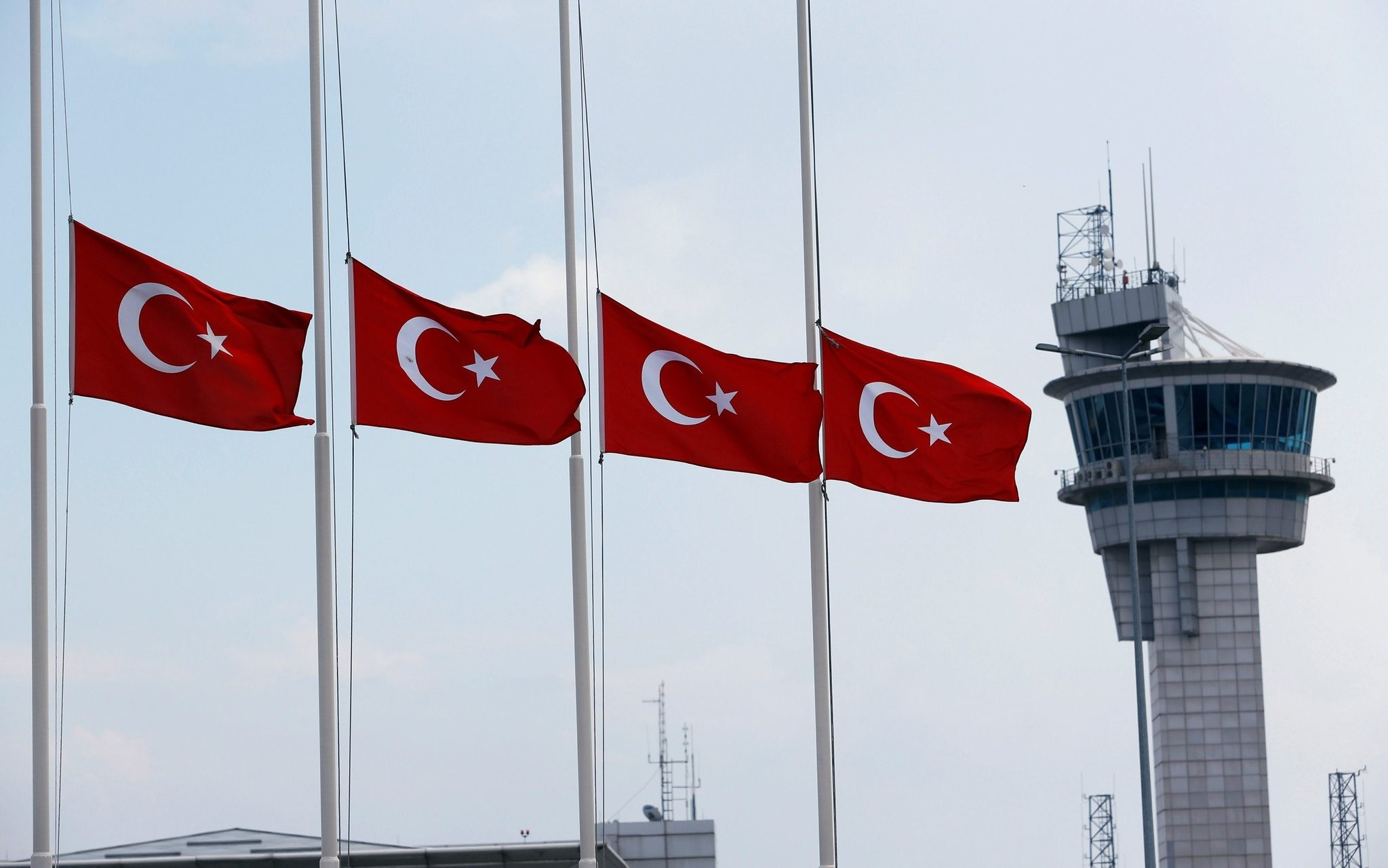 Turkish flags, with the control tower in the background, fly at half mast at the country's largest airport, Istanbul Atatu00fcrk, following the June attack there. (Reuters Photo)