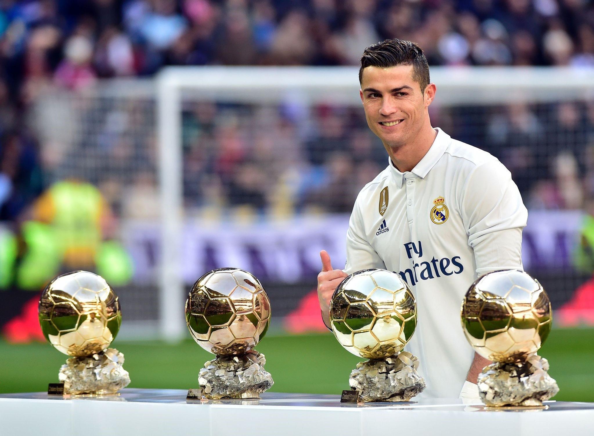 Real Madridu2019s Portuguese forward Cristiano Ronaldo poses with his four Ballon du2019Or France Football trophies before the Spanish league football match Real Madrid vs Granada at the Santiago Bernabeu stadium.
