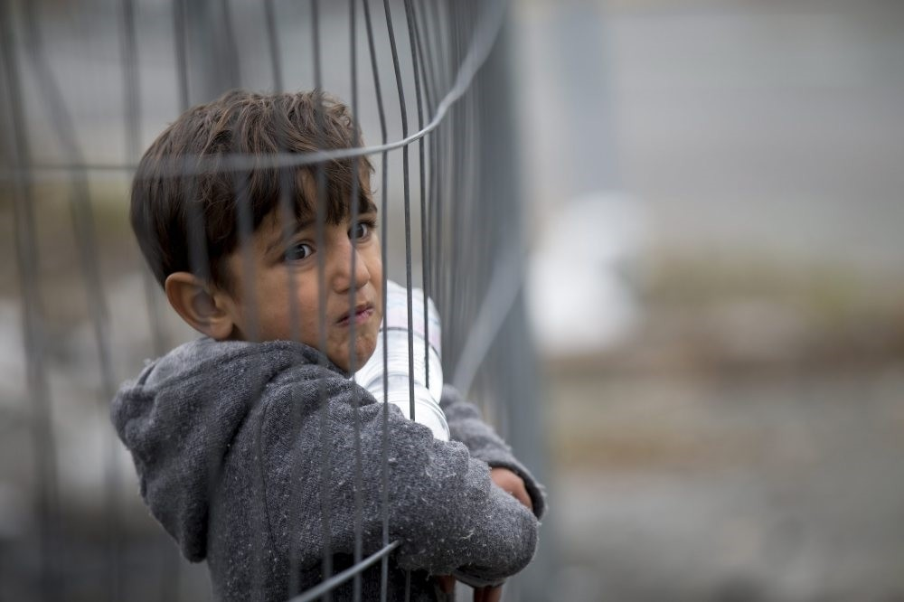 A refugee child looks through a fence in one of the alleys of the al-Kallasseh area in the eastern neighborhoods of Aleppo, Syria, Dec. 30, 2016.
