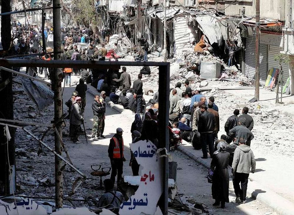 Residents wait to receive food aid distributed at the Palestinian refugee camp of Yarmouk.