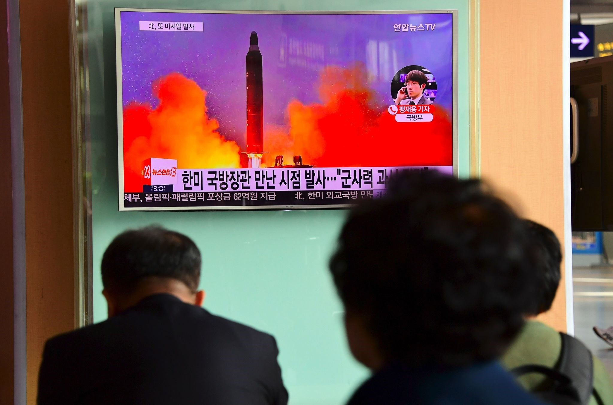 People watch a television news report showing file footage of North Korea's missile launch at a railway station in Seoul on October 20, 2016. (AFP Photo)