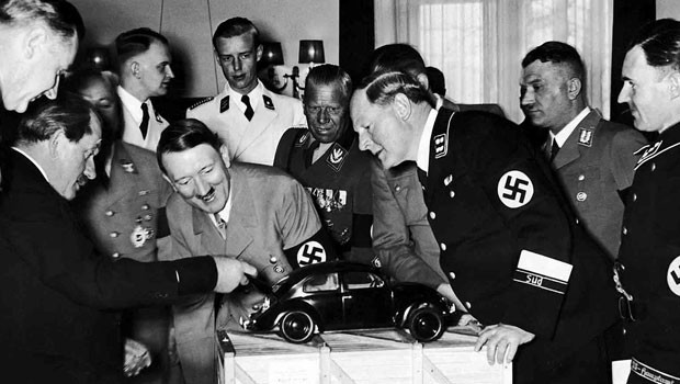 Adolf Hitler and his officials inspect a Volkswagen Beetle model