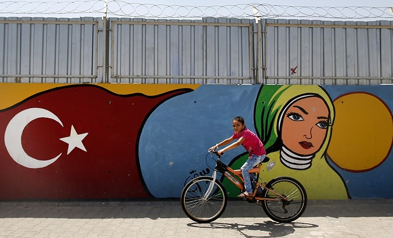 A child cycles past graffiti at the u00d6ncu00fcpu0131nar camp for Syrian refugees next to the border crossing with Syria, near the town of Kilis in southeastern Turkey, Monday, June 20, 2016 (AP Photo)