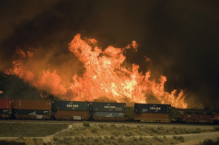 Flames erupt on a hillside alongside one of the main rail routes connecting Southern California with points north and east as a wildfire rages out of control in Cajon Pass north of Devore, Calif., Tuesday, Aug. 16, 2016. (AP Photo)