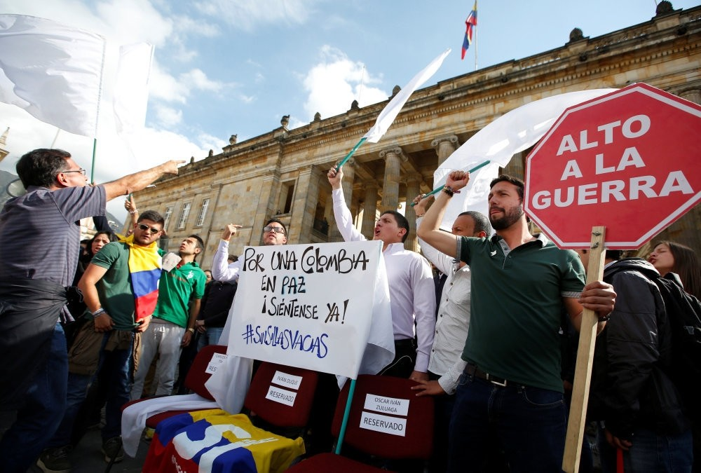 University students and supporters of the peace deal signed between the government and Revolutionary Armed Forces of Colombia (FARC) guerillas protest during a rally in front of Congress in Bogota. The sign reads: ,For Colombia Peace, sit here.,