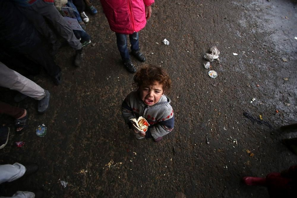 A Syrian child, who fled with his family from rebel-held areas in the city of Aleppo, reacts as he holds a sandwich on December 1, 2016, at a shelter in the neighbourhood of Jibrin, east of Aleppo. (AFP Photo)