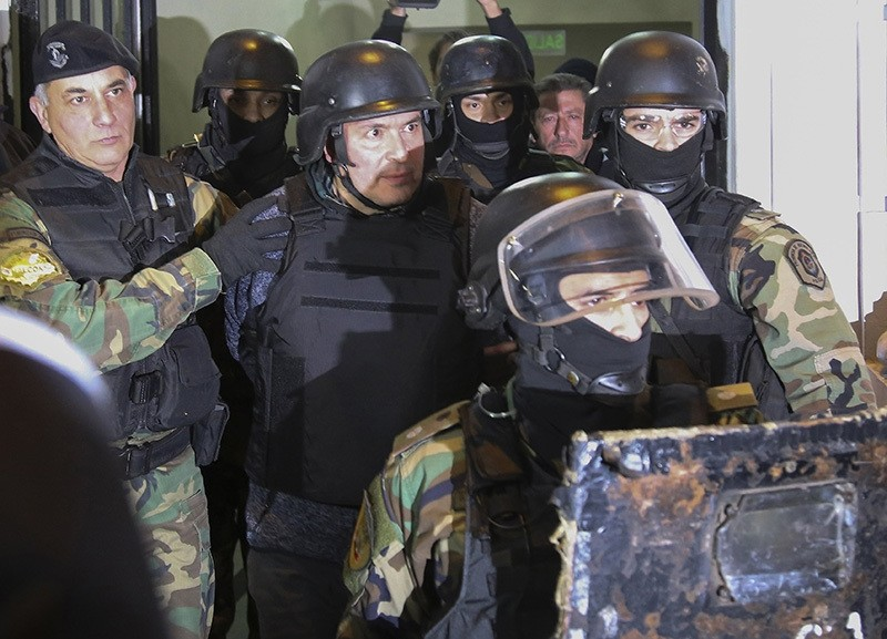 Jose Lopez (C) is taken into custody after being arrested in General Rodriguez, province of Buenos Aires on June 14, 2016 while he was trying to hide 160 packages with more than eight million dollars in the garden of a nunnery. (AFP Photo)