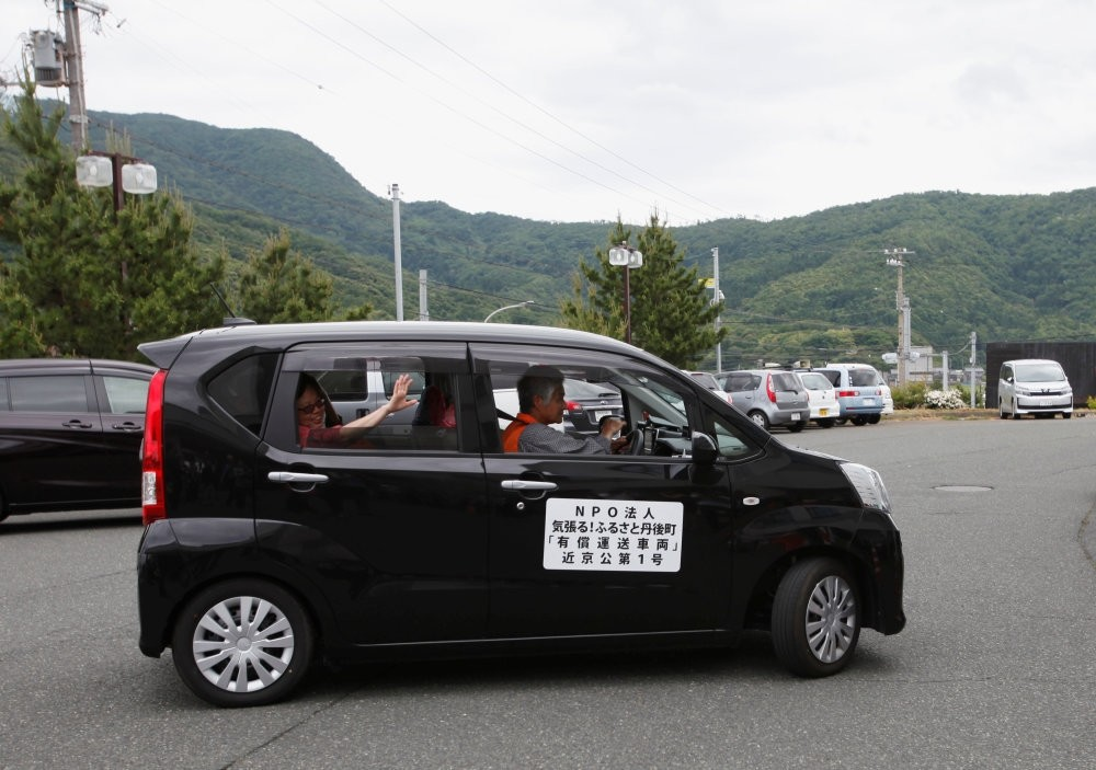 A tourist from Singapore (L), who is the first user of the car sharing service supported by Uber in Kyotango, Japan, waves from the car.