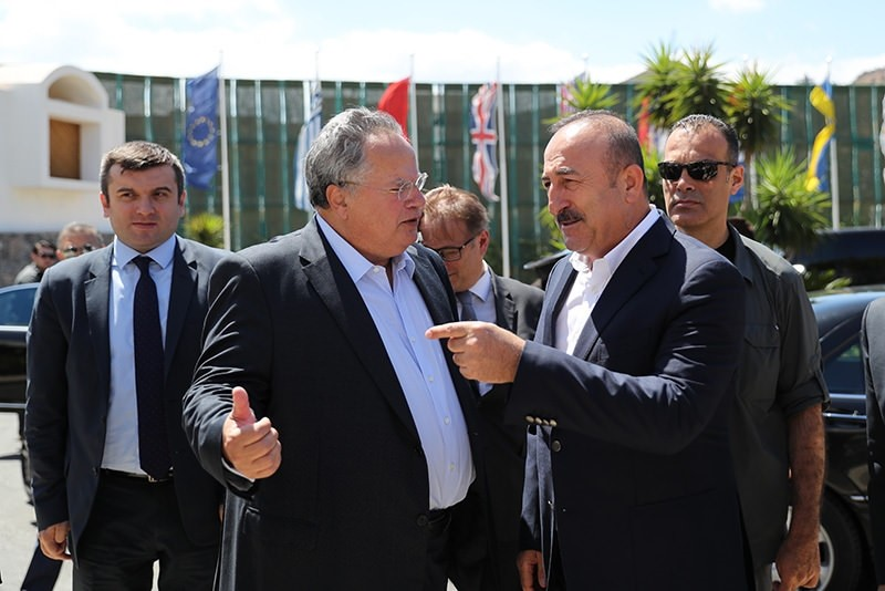 Turkish FM Mevlu00fct u00c7avuu015fou011flu (R) was greeted by his Greek counterpart Nikos Kocias at the entrance of the hotel in the town of Elounda. (AA Photo)