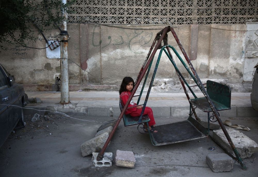 A Syrian girl playing on a swing in the moderate-held town of Douma, east of capital Damascus on the first day of Ramadan Bayram holiday that marks the end of the Muslim holy fasting month of Ramadan July 6, 2016. (AFP Photo)