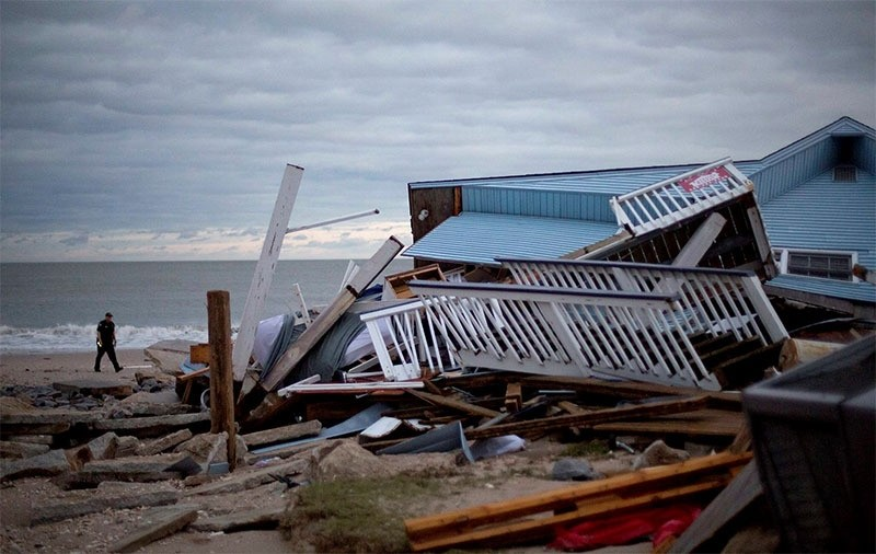 A police officer walks past the remnants of a home leveled by Hurricane Matthew after it hit the tiny beach community of Edisto Beach, S.C., Saturday, Oct. 8, 2016. (AP Photo)