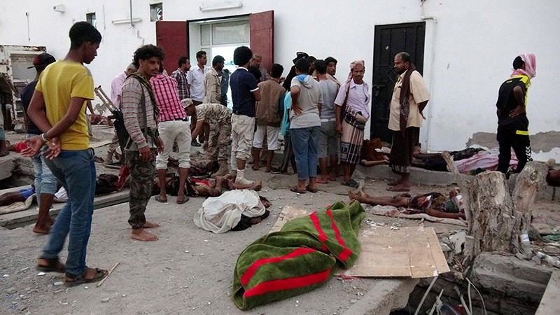 Soldiers and people gather by the bodies of soldiers killed by a suicide bomber at a base in the southern port city of Aden, Yemen on Dec. 10, 2016. (Reuters Photo)