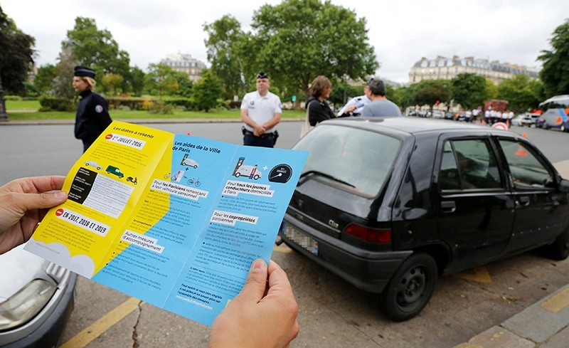 A man holds a leaflets as French police speaks to a driver with a car older than 20 years to explain a new law to fight air pollution at the Place de la Nation square in Paris, France, July 1, 2016 (Reuters Photo)