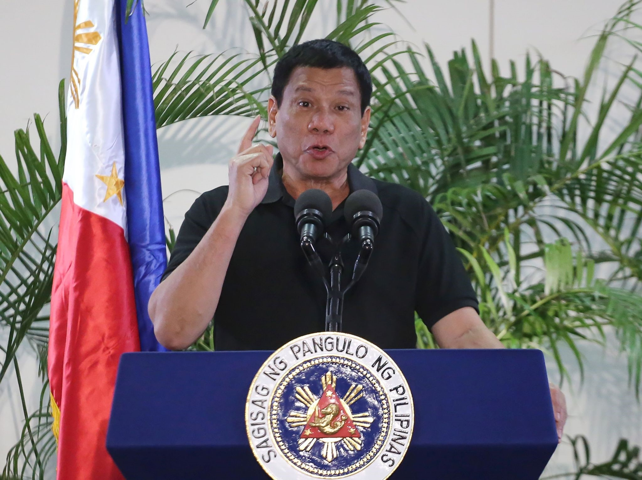 Philippines President Rodrigo Duterte delivers a speech at the Davao international airport terminal building early on September 30, 2016, shortly after arriving from an official visit to Vietnam. (AFP Photo)