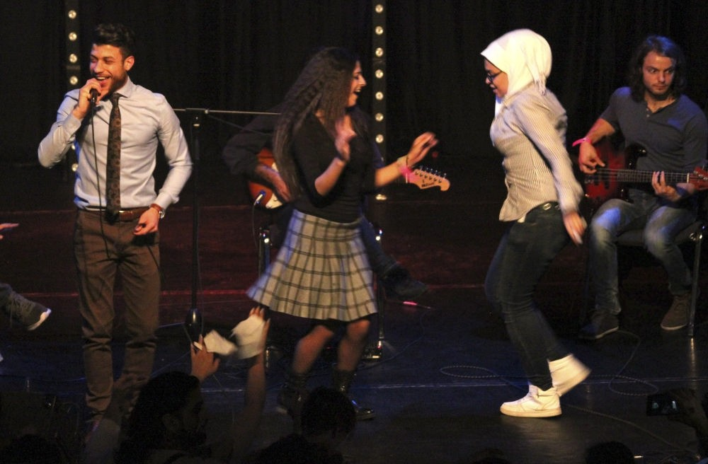 A group of women dance on stage during the performance by the Syrian band Musiqana at the u201cRefugees in concertu201d event in Berlin.