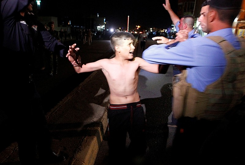 Iraqi security forces detain a boy after removing a suicide vest from him in Kirkuk, Iraq, August 21, 2016 (Reuters Photo