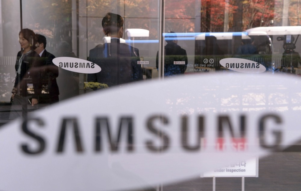 Employees walk past logos of Samsung Group at its headquarters in Seoul, South Korea.