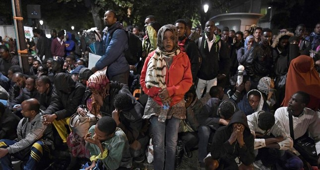 Migrants gather and wait before being evacuated from a makeshift migrant camp set up between the metro stations of Jaures and Stalingrad, in Paris, on Sept. 16.
