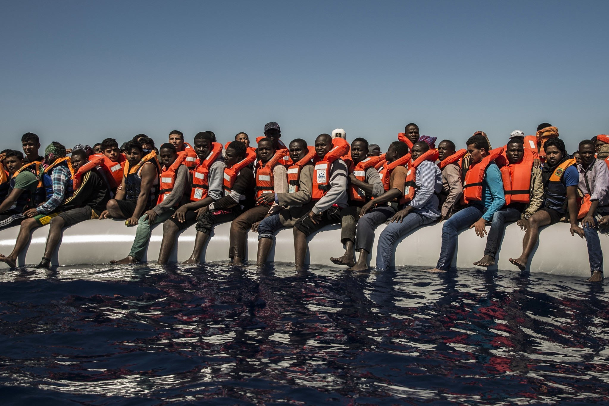 In this Tuesday July 19, 2016 photo, refugees and migrants from Eritrea, Mali, Bangladesh and other countries wait on board a dinghy to be rescued in the Mediterranean Sea, 27 kilometers (17 miles) north of Sabratha, Libya. (AP Photo)