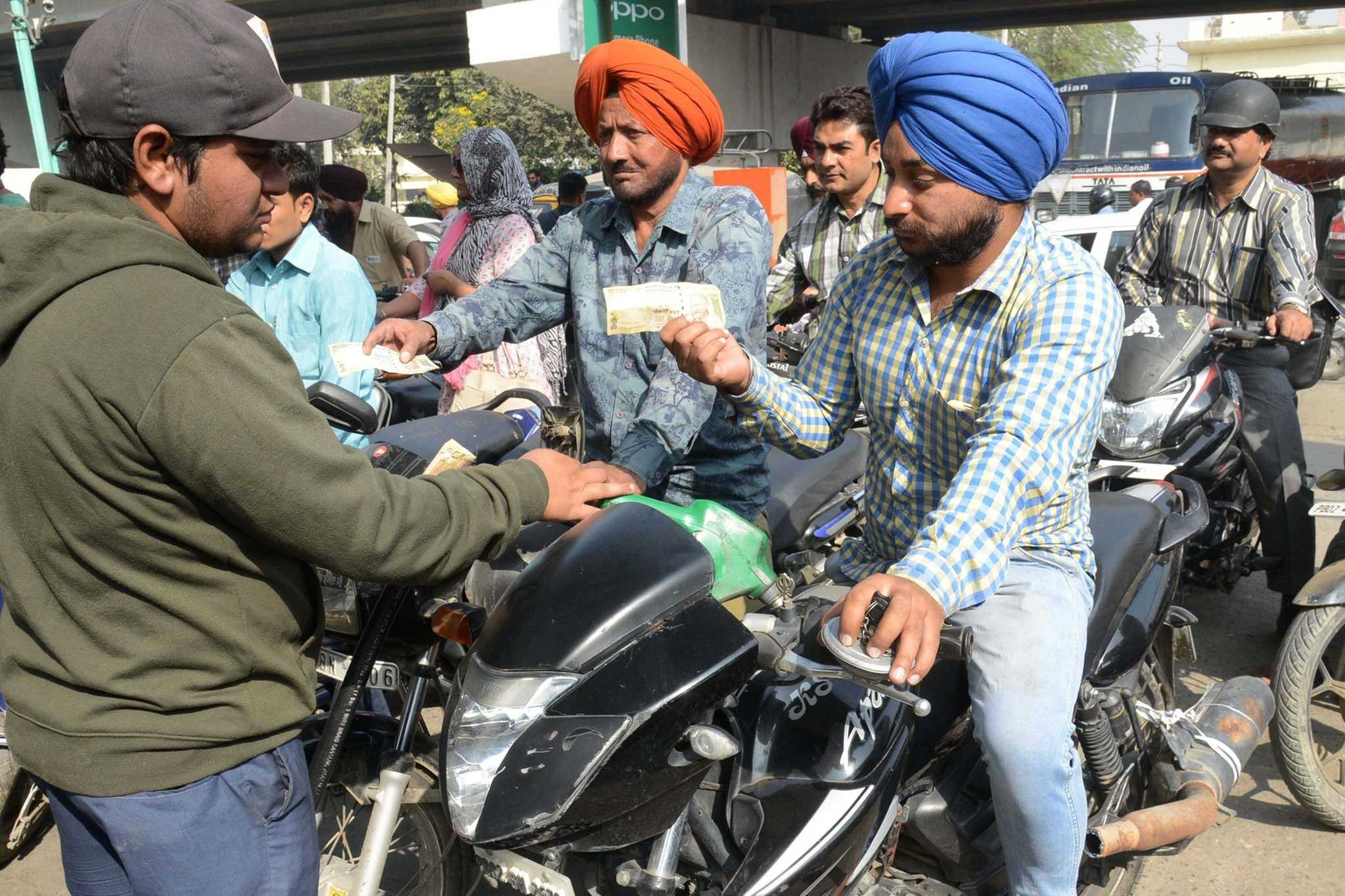 Indian motorists pay with 500 rupee notes at a fuel station in Amritsar. ATMs were closed and many are likely to remain shut today as banks prepare for the flood of people seeking to exchange larger banknotes.