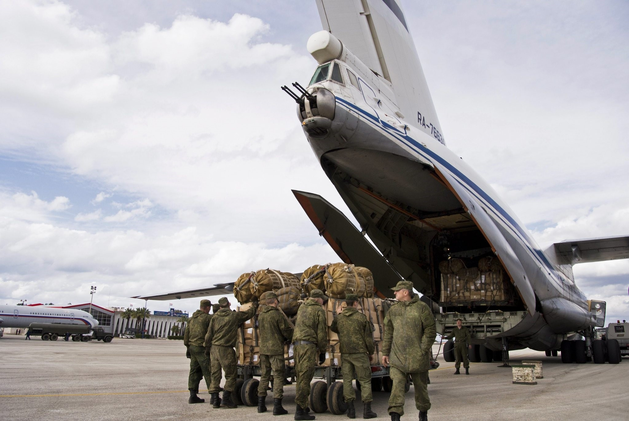 Russian air force personnel prepare to load humanitarian cargo on board a Syrian Il-76 plane at Hemeimeem air base in Syria. ((AP Photo)