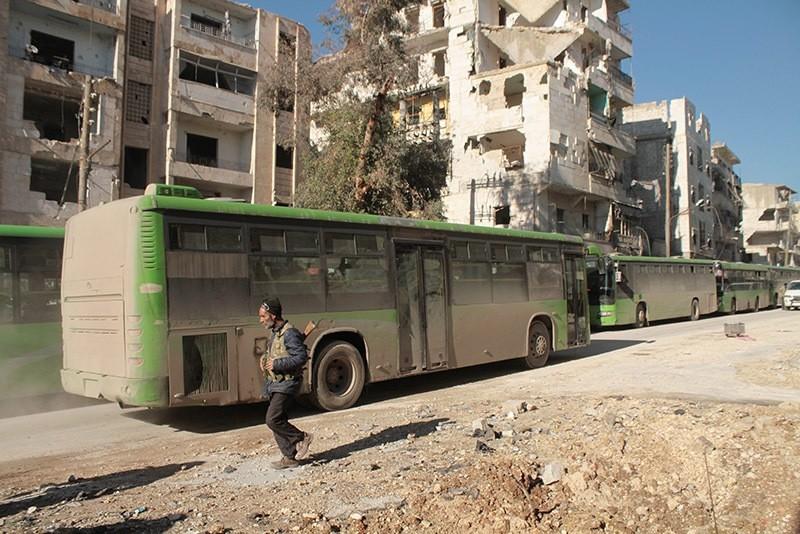 An armed man walks next to evacuation buses, Aleppo, Syria. (EPA Photo)