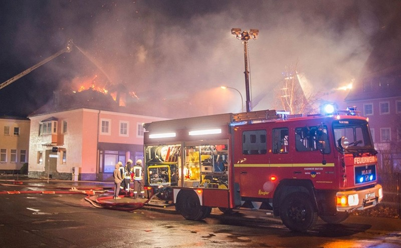 This file photo taken on February 21, 2016 shows fire fighters trying to extinguish a fire at a former hotel that was under reconstruction to become a home for asylum seekers on February 21, 2016 (AFP Photo)