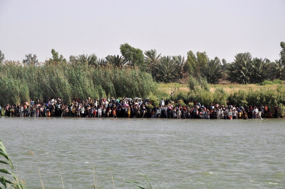 Internally displaced civilians from Fallujah flee their homes, gathering on the edge to cross the Euphrates River.