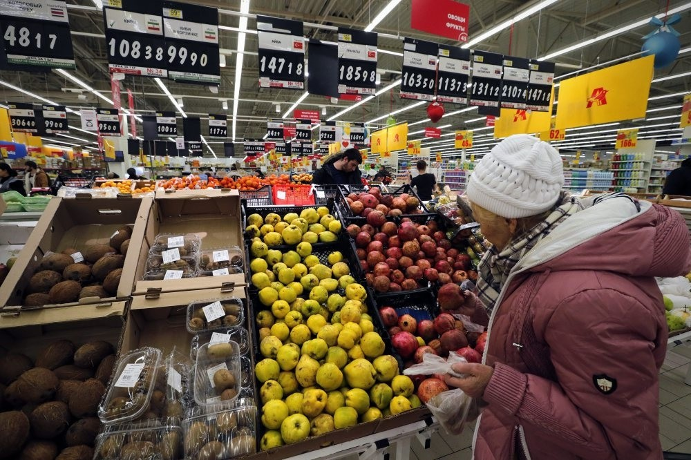 A Russian woman chooses fruits imported from Turkey at a supermarket.