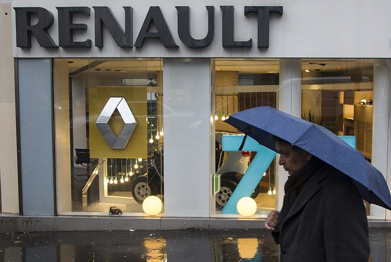 This file photo dated Dec. 14, 2012 showing a pedestrian with an umbrella in front of a Renault dealership in Paris, France. (EPA Photo)