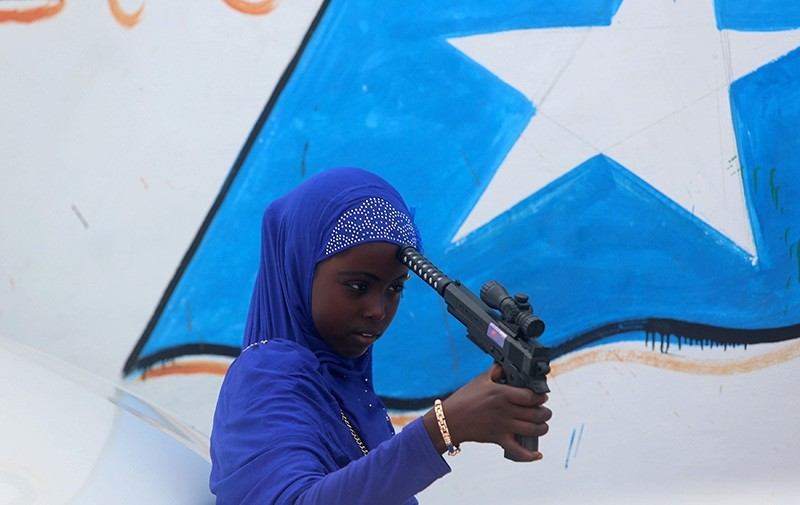 A Somali girl plays with a toy gun after attending Eid al-Fitr prayers to mark the end of the fasting month of Ramadan in Somalia's capital Mogadishu, July 6, 2016. (Reuters Photo)