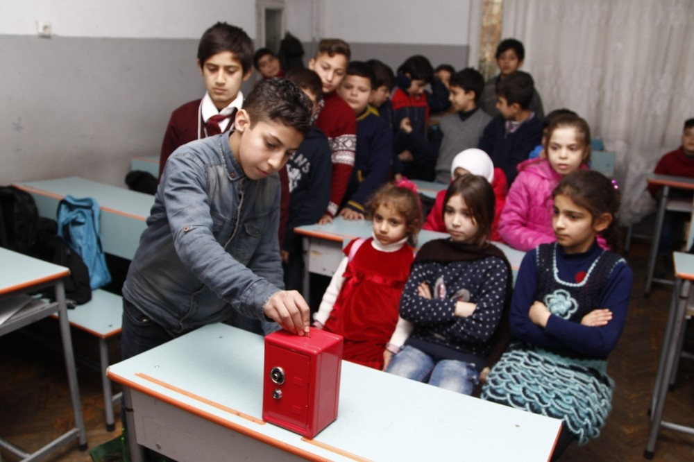 Young Syrian students putting their savings in a donation box in their classroom. Syrians in Turkey are concerned about well-being of their relatives and friends in Aleppo.