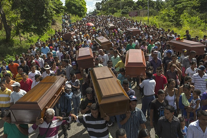 Villagers carry remains of 9 slain men from a fishing family to the cemetery in Cariaco, Venezuela, Nov. 13, 2016. 5 law enforcement officers were charged with killing these men, who were widely thought to have belonged to a piracy gang. (AP Photo)