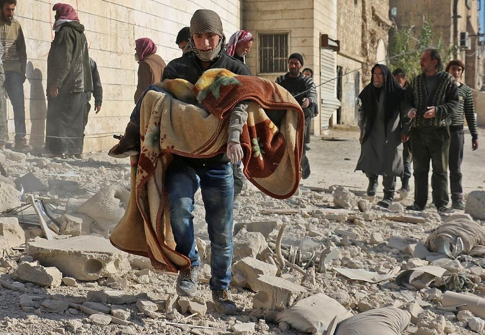 A man carries the covered body of a boy following a reported barrel bomb attack on the Bab al-Nairab neighbourhood of the northern Syrian city of Aleppo on November 24, 2016. (AFP Photo)
