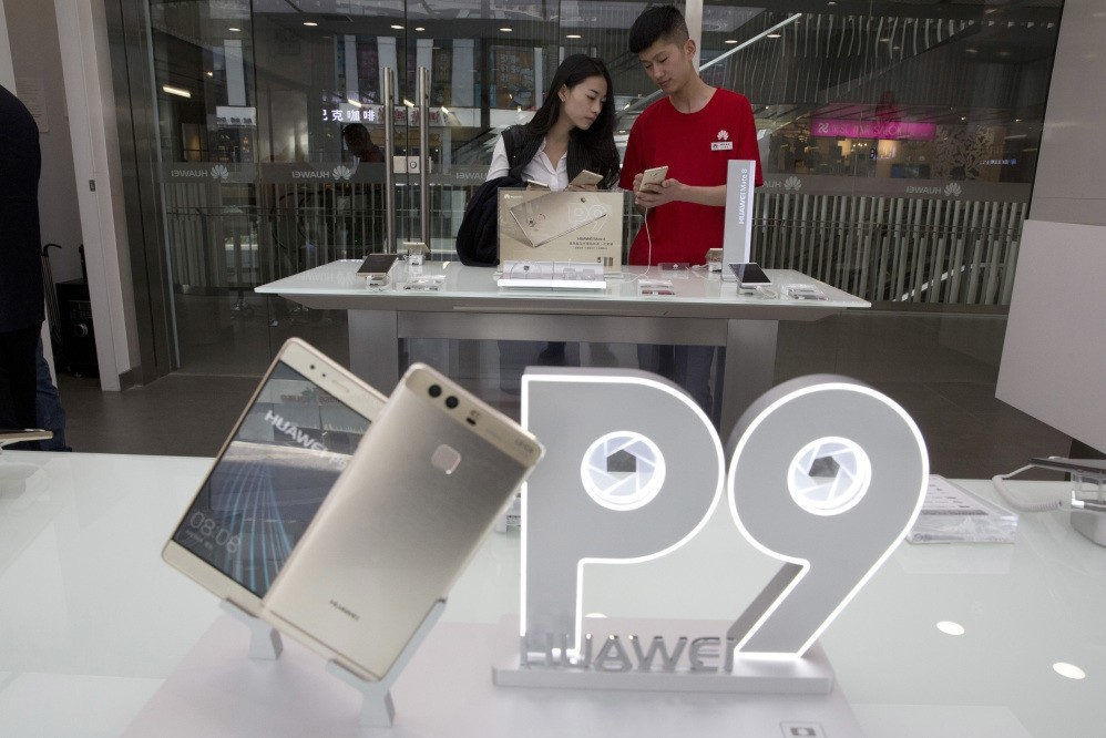 A sales person chats with a customer at a Huawei retail shop with an advertisement for the P9 in Beijing, China.
