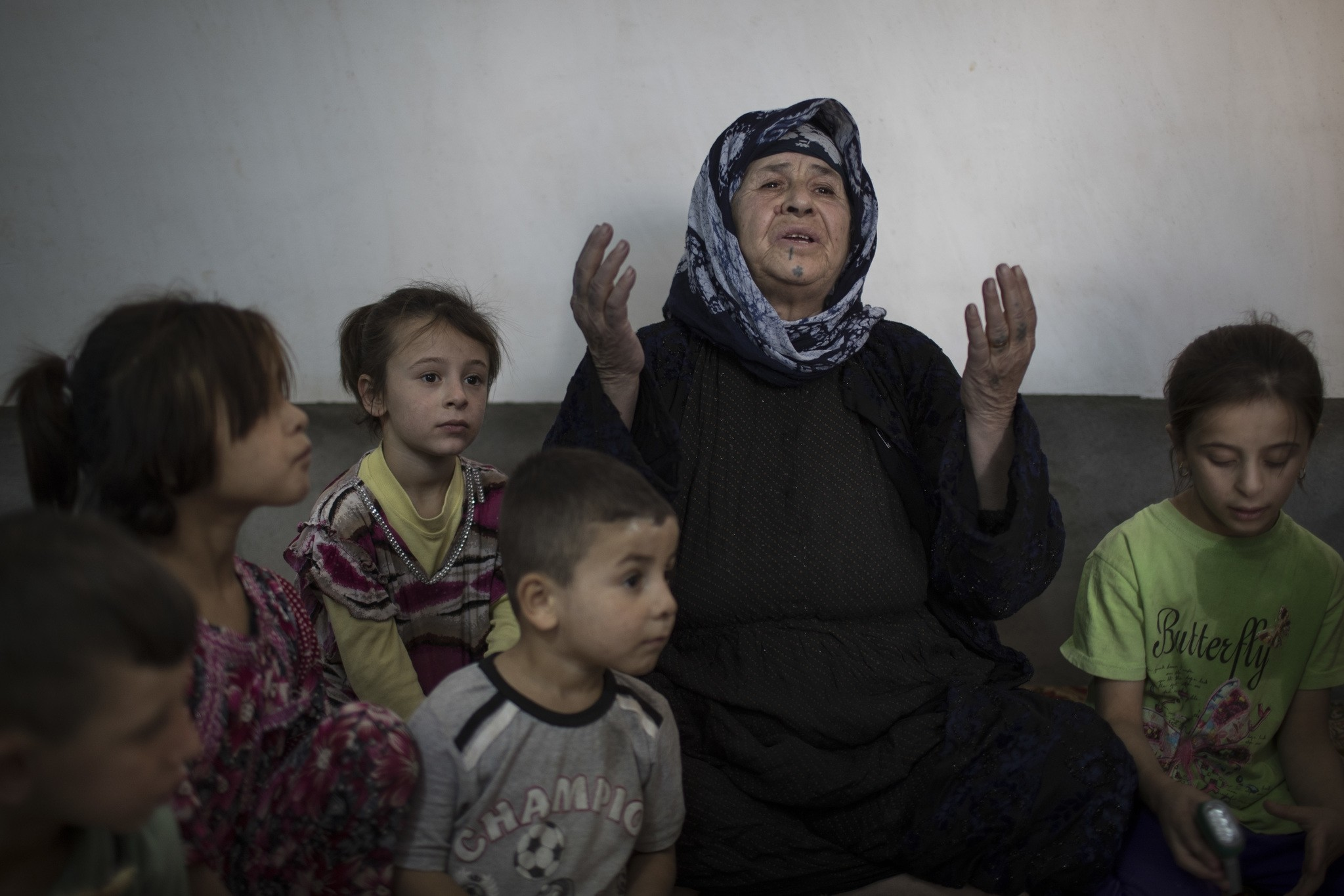 Husna Abbas sits with her grandchildren inside her home in the Yahyawa camp for internally displaced Turkmen on the outskirts of Kirkuk, Iraq, Sunday, Oct. 30, 2016. (AP Photo)