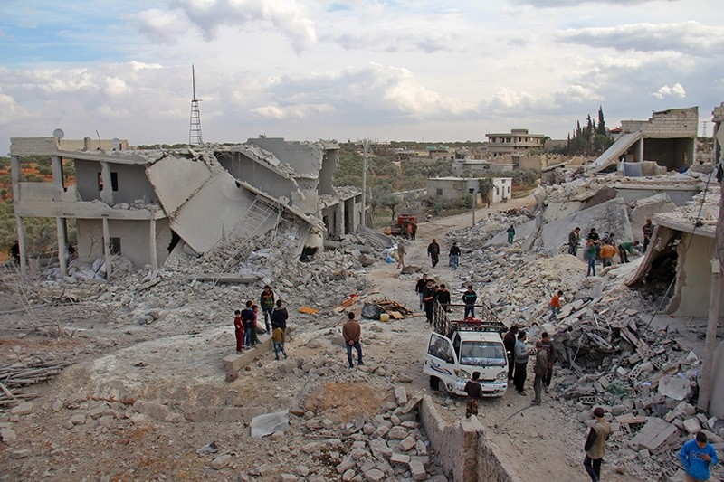 Civilians check destroyed buildings in the Syrian village of Kfar Jales, on the outskirts of Idlib, following air strikes by regime and Russian warplanes on Nov. 16, 2016. (AFP Photo)