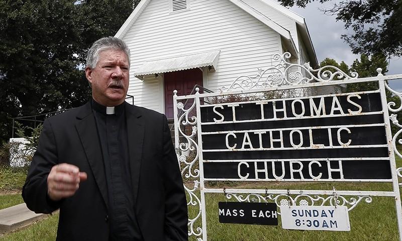 Rev. Greg Plata, speaks outside the St. Thomas Catholic Church that he pastors Friday, Aug. 26, 2016 in Lexington (AP Photo)