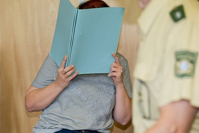 Defendant Andrea G. , who is accused of murder, covering her face with a folder, in the court room of the regional court in Coburg, Germany, Tuesday July 12, 2016. (AP Photo)