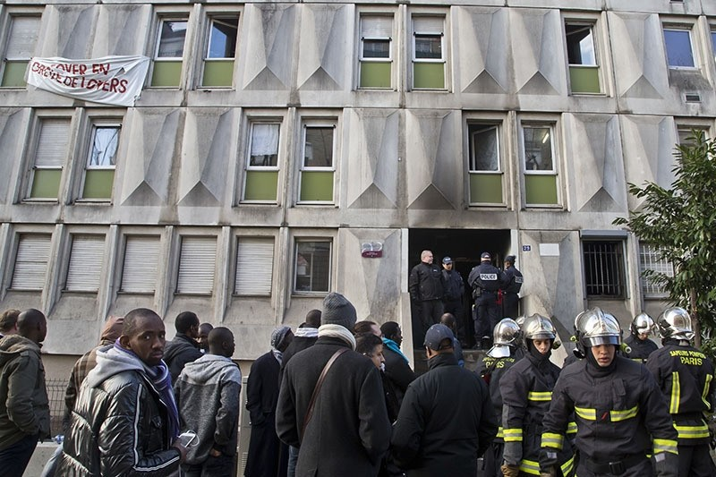 Migrants and fire fighters gather outside a migrant workers' center after a fire broke out in Bouglogne-Billancourt, west of Paris, Friday, Dec. 16, 2016. (AP Photo)