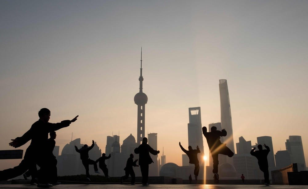People do morning exercises in front of the skyline of the Lujiazui Financial District in Pudong in Shanghai.