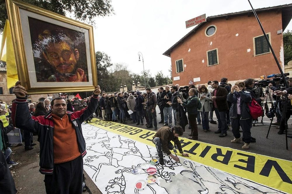 A man holds up a portrait of Giulio Regeni, the Italian student slained in Cairo, as several dozen people stage a sit-in outside Egypt's embassy in Rome. (AP Photo)
